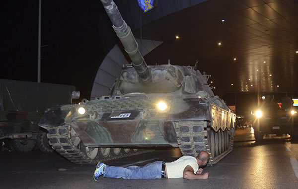 Man lying down in front of tank